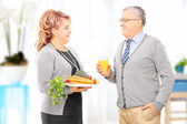Couple holding dish full of vegetables — Stock Photo
