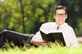 Male on grass with book — Foto Stock