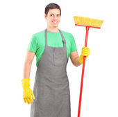 Male cleaner holding brush — Stockfoto