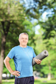 Man holding an exercising mat — Stock Photo