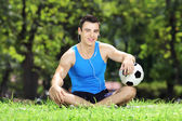 Male athlete sitting down on grass — Stock Photo