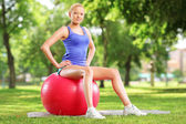 Female athlete sitting on a ball — Stockfoto