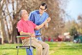 Nurse checking pulse of senior — Stock Photo