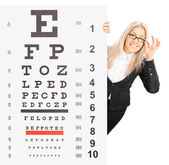 Woman standing behind an eyesight test — Stock Photo