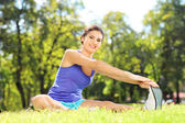 Female athlete stretching in park — Stock Photo