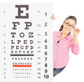Girl standing behind eyesight test — Stock Photo