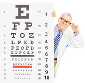 Male optician standing behind eyesight test — Stock Photo