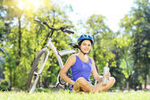 Female biker in park — Stock Photo