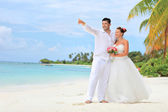 Bride and groom embracing on beach — Стоковое фото