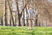 Senior gentleman with walker in park — Stock Photo