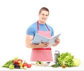 Male chef reading cookbook — Stock Photo