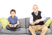 Grandfather with nephew playing vide — Stock Photo