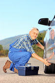 Mechanic changing car tyre on an open road — Stock Photo