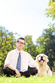 Smiling man on green grass with dog — Stock Photo