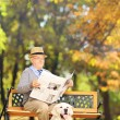 Senior man reading newspaper with dog — Stock Photo
