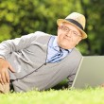 Senior man on grass working on laptop — Stock Photo #45890481