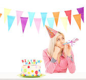 Sad birthday girl with cake — Stock Photo