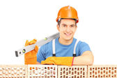 Male construction holding bubble level — Stock Photo