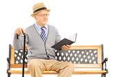 Senior man reading a book — Stok fotoğraf