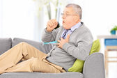 Man seated on sofa coughing — Stock Photo