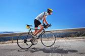 Cyclist riding bike uphill — Stock Photo
