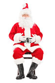 Santa claus sitting on wooden chair — Foto Stock