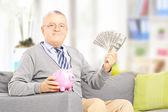 Senior holding a piggy bank and money — Stock Photo