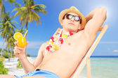 Man holding a cocktail on a sun lounger — Stock Photo