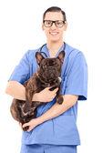 Mâle vétérinaire tenant un chien — Photo