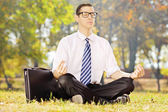 Young businessperson seated on a grass meditating in a park — Stock Photo