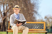 Gentleman with book on bench — Stockfoto