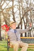 Elderly holding tulips and taking selfie — Stock Photo
