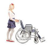 Jong meisje duwen rolstoel — Stockfoto