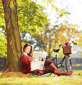 Woman on grass reading a newspaper — Stock Photo