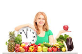 Woman with apple, clock and fruits — Stock Photo