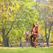 Female on bicycle in park — Stock Photo