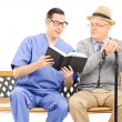 Medical professional reading to elderly — Stock Photo #46591857
