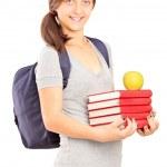 Schoolgirl holding pile of books — Stock Photo #46592063