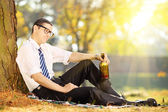Businessman sitting on grass with bottle — Stock Photo