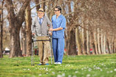 Medical professional helping senior in park — Stock Photo