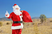 Santa hitchhiking on open road — Stock Photo