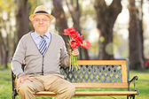 Senior man with red tulips — Stock Photo