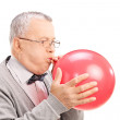 Mature man blowing up balloon — Stock Photo #48316241