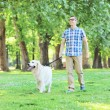 Man walking dog in park — Stock Photo #48318309