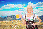Woman holding beer in mountains — Stock Photo