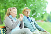 Mature couple blowing bubbles — Stock Photo