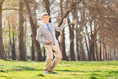 Overjoyed senior playing air guitar — Stock Photo