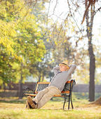 Relaxed pensioner sitting in park — Stock Photo