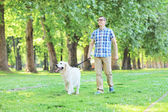 Man walking dog in park — Stock Photo