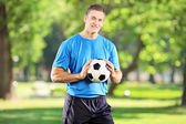 Man holding football in park — Stockfoto